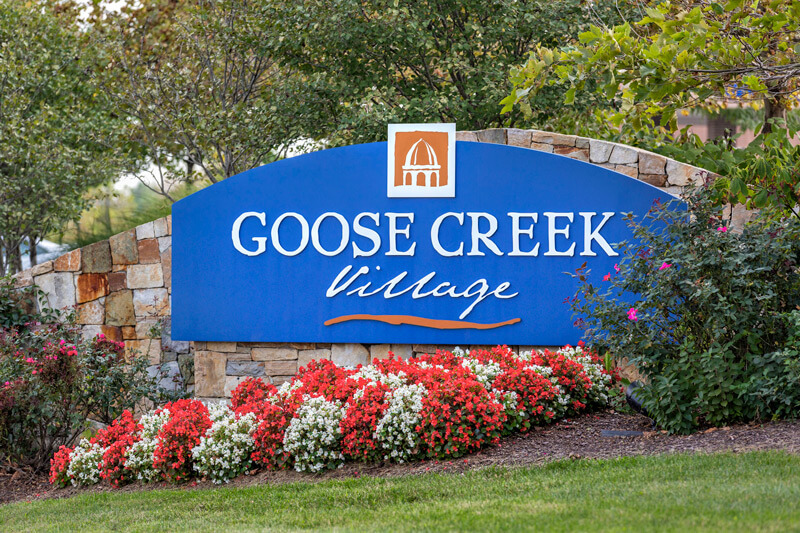Goose Creek Village monument sign at community entrance with flower beds in front