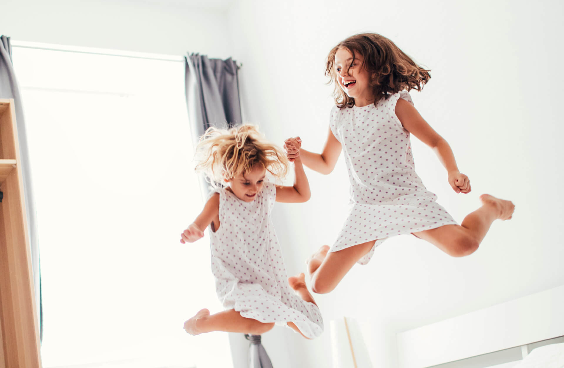 two little girls in dresses jumping on a bed and smiling