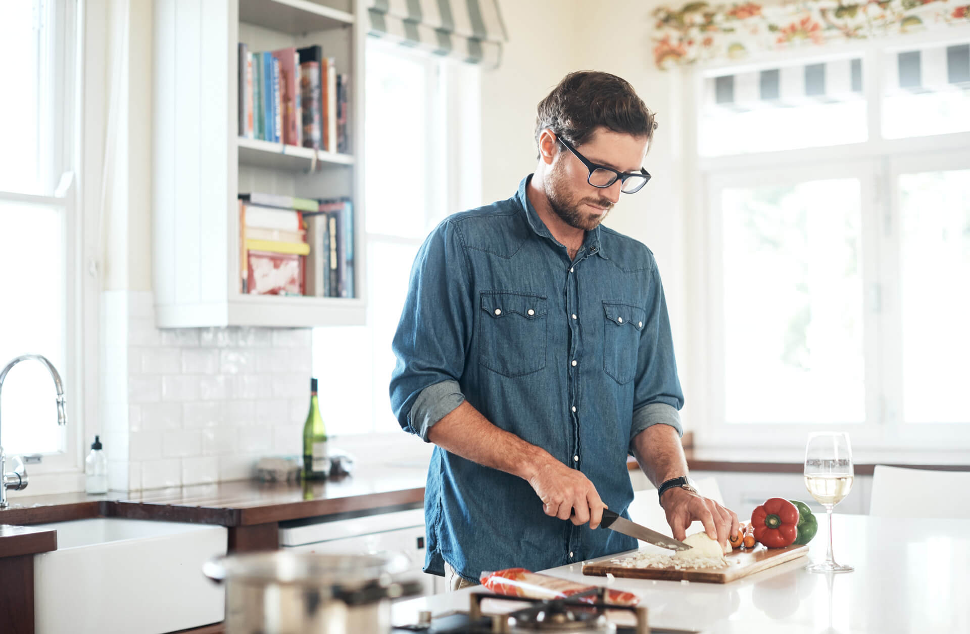 mean in denim shirt and glasses cutting onions in a home kitchen