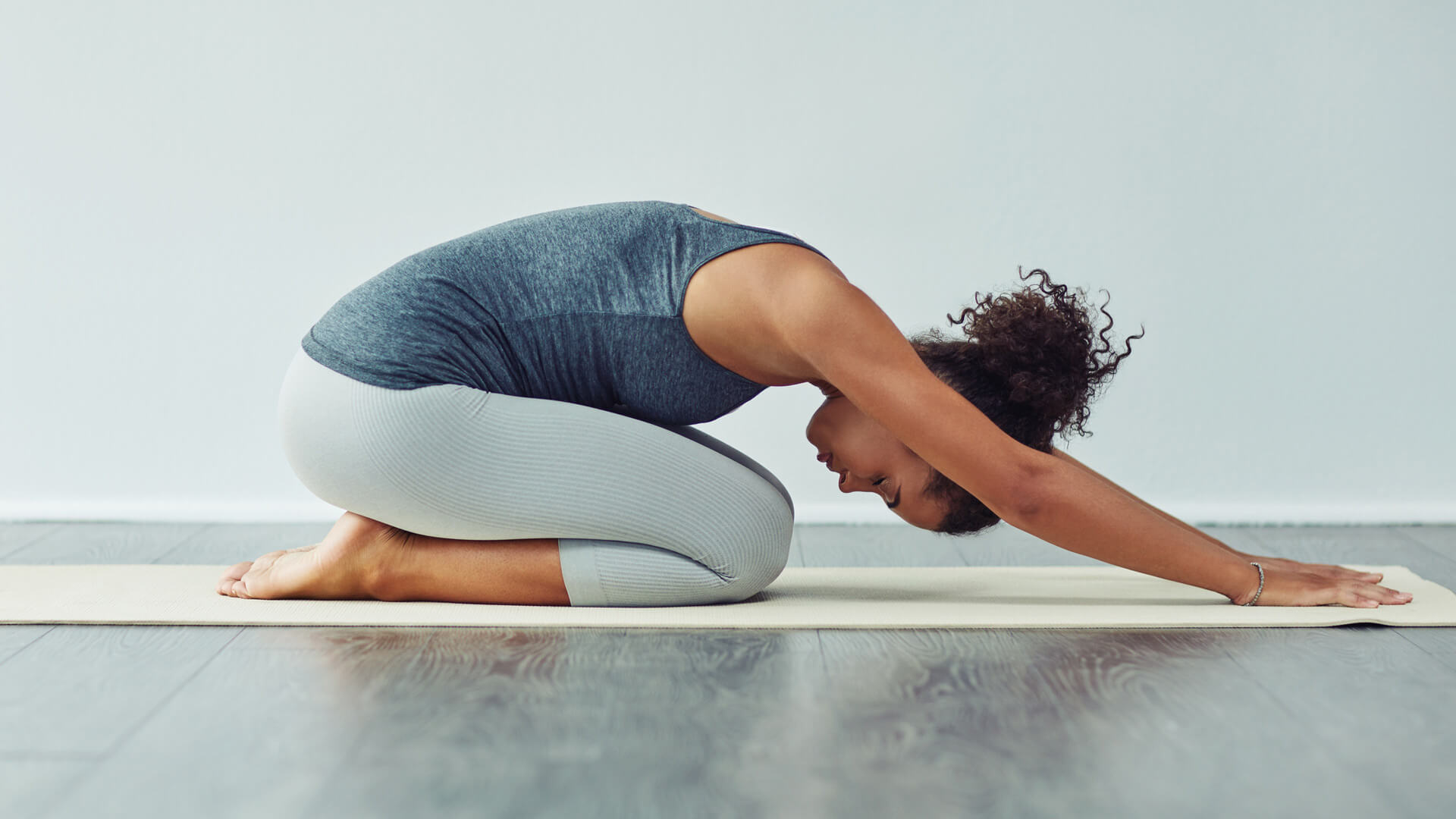 woman in yoga attire on mat in downward dog pose