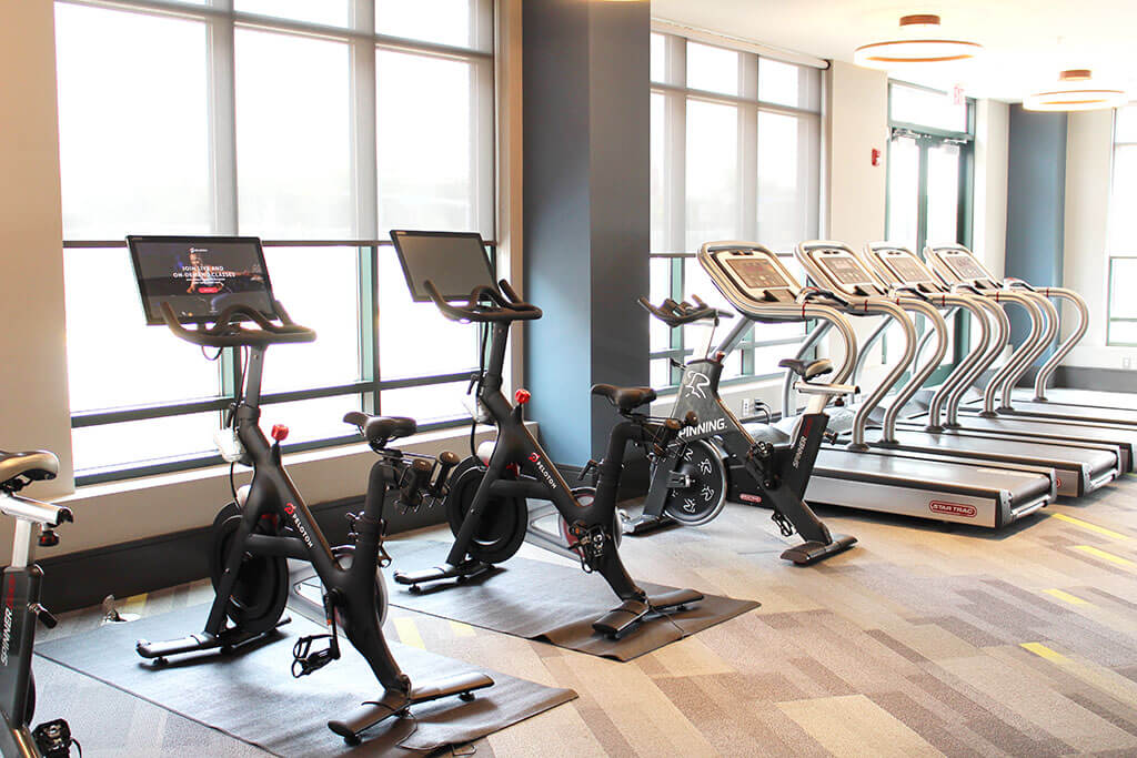 photo of the fitness center at The Heights at Goose Creek Village apartments in Ashburn, VA with a row of spin bikes next to a row of treadmills