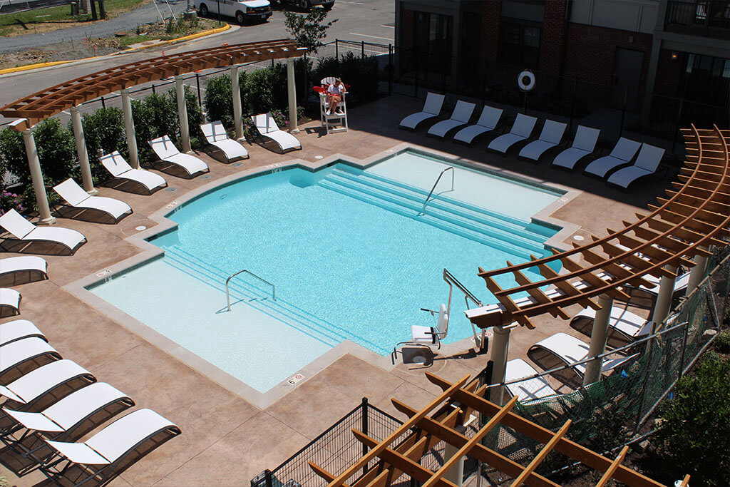 overhead photo of the swimming pool at The Heights at Goose Creek Village apartments in Ashburn, VA with lounge chairs all around and wooden pergolas to the east and west of pool
